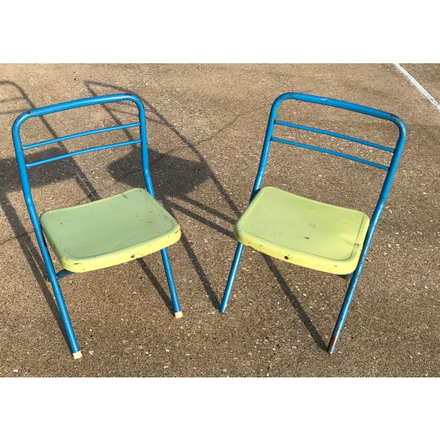 Two colorful metal folding children's chairs. The original colors of yellow and blue. Paint is peeling, one is missing its...
