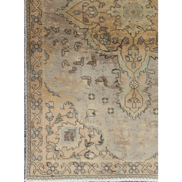 This Semi Antique rug features a center medallion design in a neutral color palette with brown outlines. Colors include...