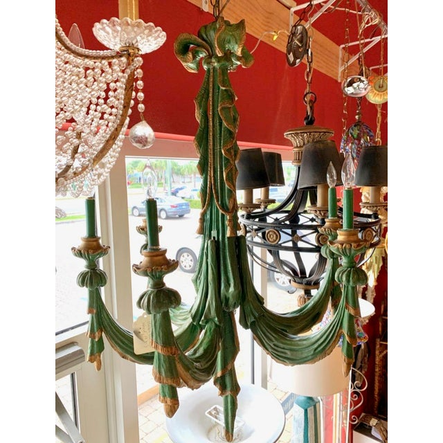 Vintage wooden chandelier. Hand carved to resemble swags of fringed cloth. Pairs of arms attach to mortices in the center...