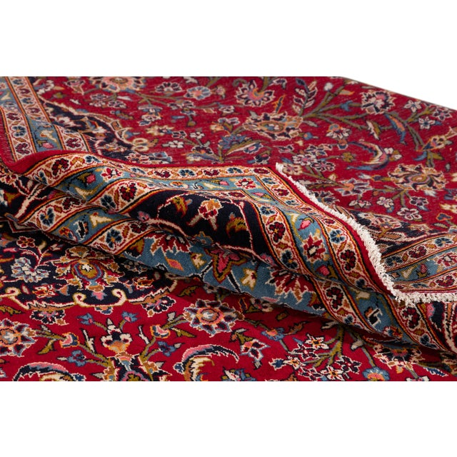 A vintage hand-knotted Persian kashan rug with a floral medallion design on a red field. This piece has great detailing...