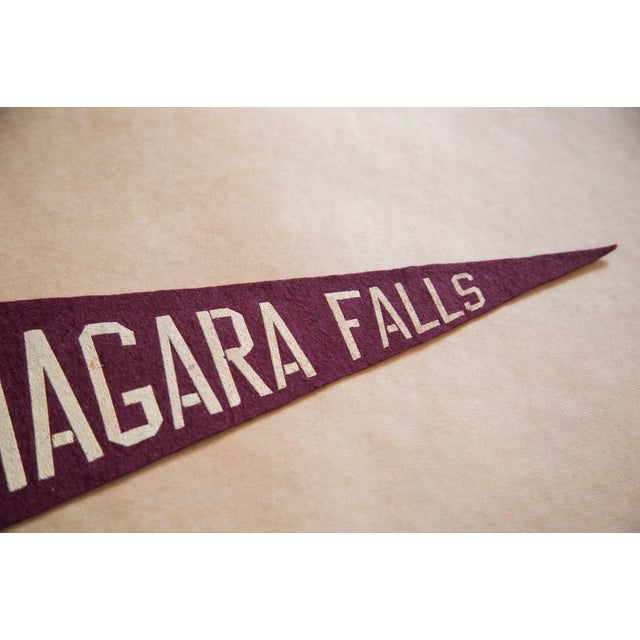 ":: Niagara Falls felt flag banner with imagery of a maple leaf and the British flag, above which reads ""Canada"". Circa..."