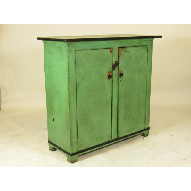 An early 19th-C. American Federal painted cupboard with original apple green painted finish with black trim and two doors...