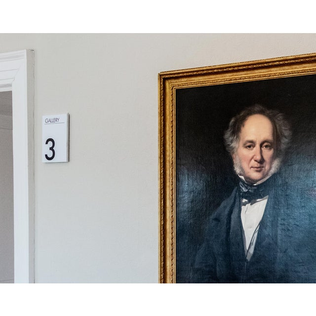 An interior photograph of a painting, a local Reverend. The painting hangs in the gallery of an old English country house....