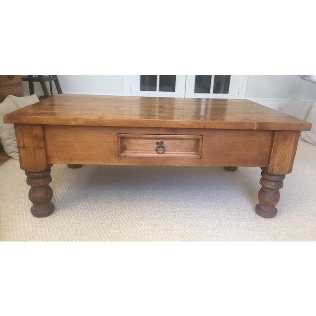 Antique solid wood coffee table with a warm dark stain and protective shellac. The detailed legs are legacy signature bun...