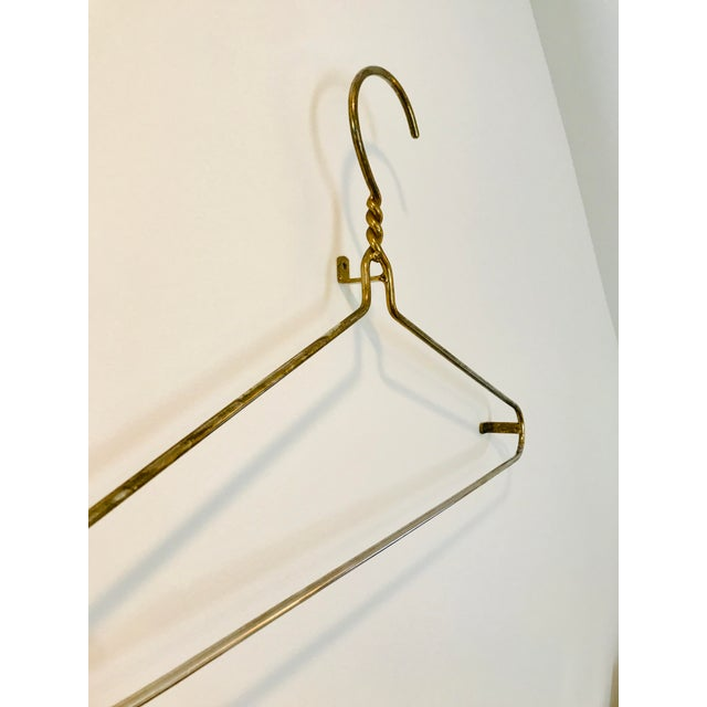 Fun and funky oversized brass plated hanger. Mounts to the wall via 3 nail holes on back side. Would be darling in laundry...