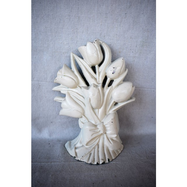 A vintage iron door stop painted white in the shape of a bouquet of tulips. This arrangement will keep your door propped...