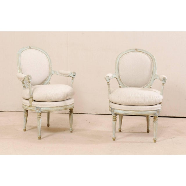 A pair of French painted wood and upholstered bergère chairs. This elegant pair of French armchairs each feature oval-...