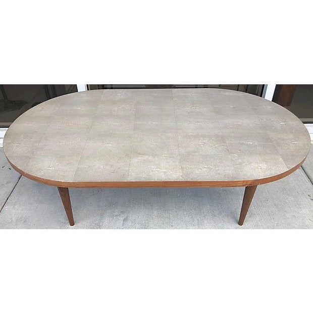 Stunning and super chic oval shagreen coffee table. The top has a wood trim as cone legs.