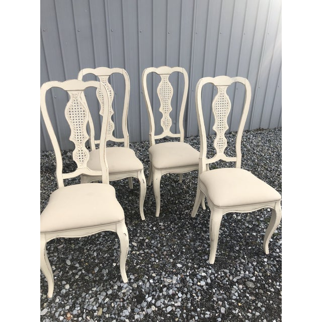 Nice vintage set of 4 shabby chic cane back dining chairs. Recently painted in a soft farmhouse white and recovered in a...
