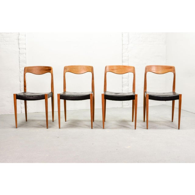 Authentic Scandinavian set of four black leatherette dining chairs early edition model 71, after N.O. Moller, produced in...