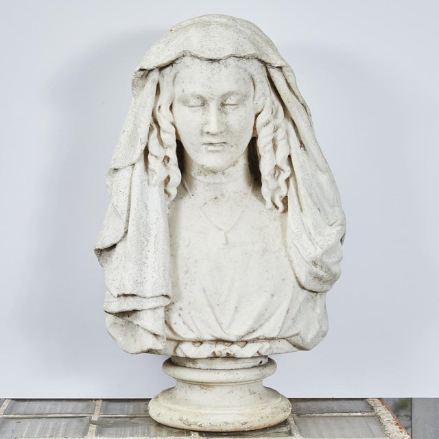 A carved stone bust of a woman.