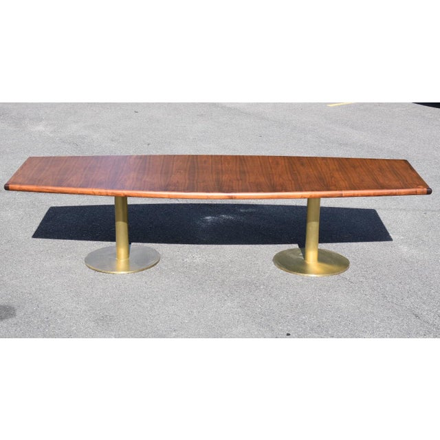 A mid-century modern walnut conference table or large dining table with two brass pedestal bases. There is minor oxidation...