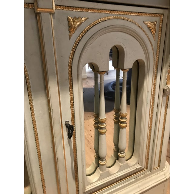 A 1870 Napoleon III console, in a beautiful painted finish with gilt accents. Two mirror front doors (with a key), and one...