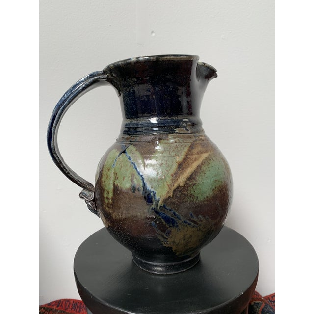 This is an oversized glazed ceramic mid century modern vintage pitcher. It's got a gorgeous navy blue, green and aubergine...