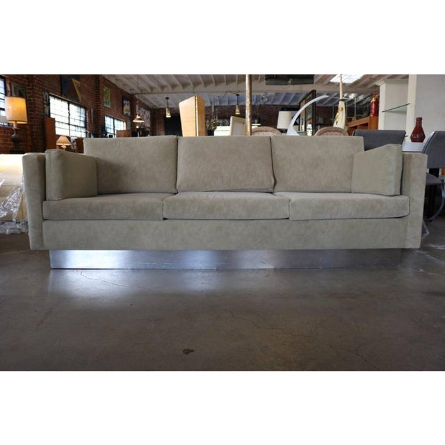 This textured suede light brown three-seat sofa rests on a chrome base, with two side cushions.