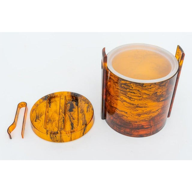 This stylish and chic Hollywood Regency style ice bucket (with tongs) dates to the 1970s and is fabricated in a faux...