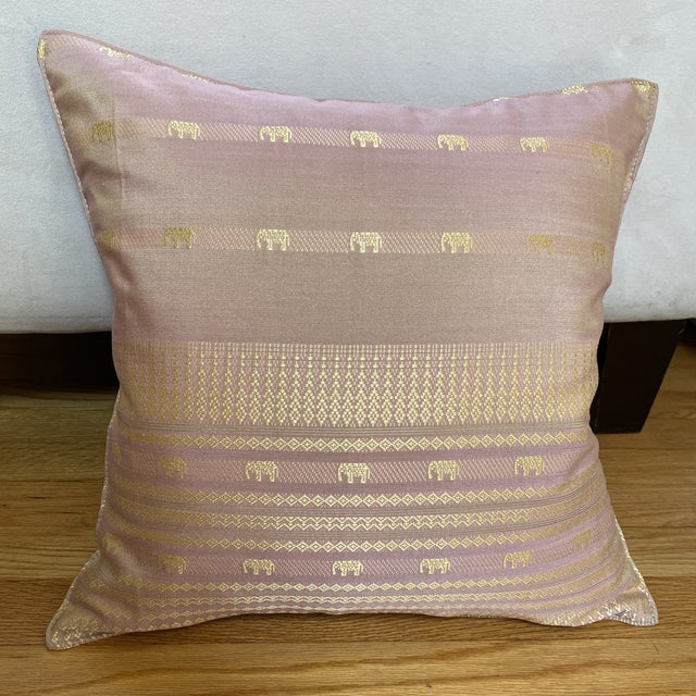 A beautiful pale pink Thai silk pillow with geometric bands and elephant motif design. It has a zipper in the back for the...