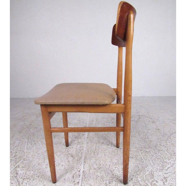 This stylish set of Scandinavian style dining chairs features vinyl seats, hardwood frames, and clean modern design....