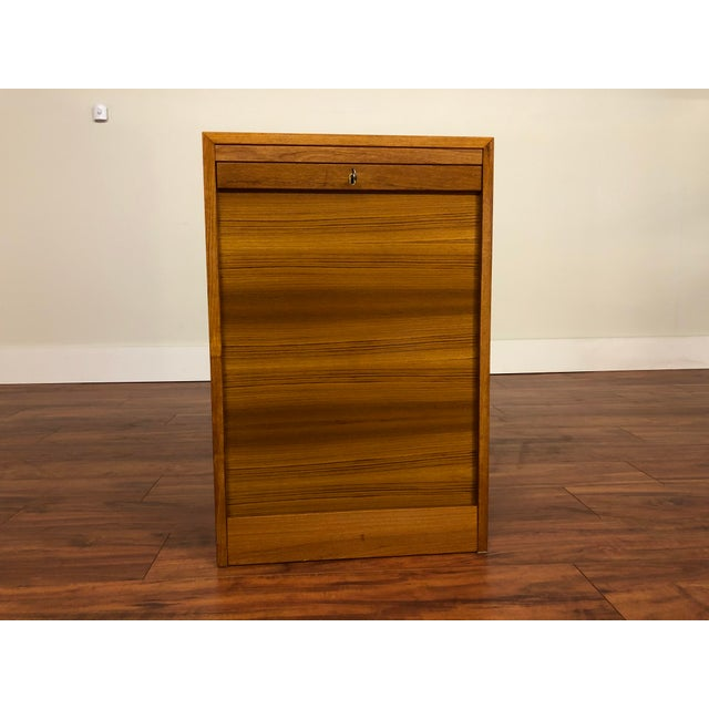 Vintage teak Danish file cabinet with tambour door. The locking drop down door disappears into the base, opening to reveal...