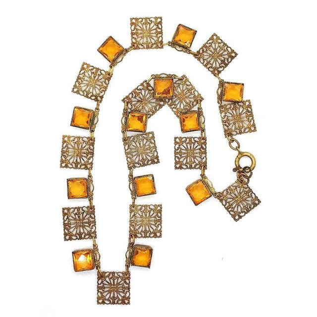 Circa 1920s, Art Deco ornate open work brass link necklace embellished with square, bezel set Czechoslovakian topaz...