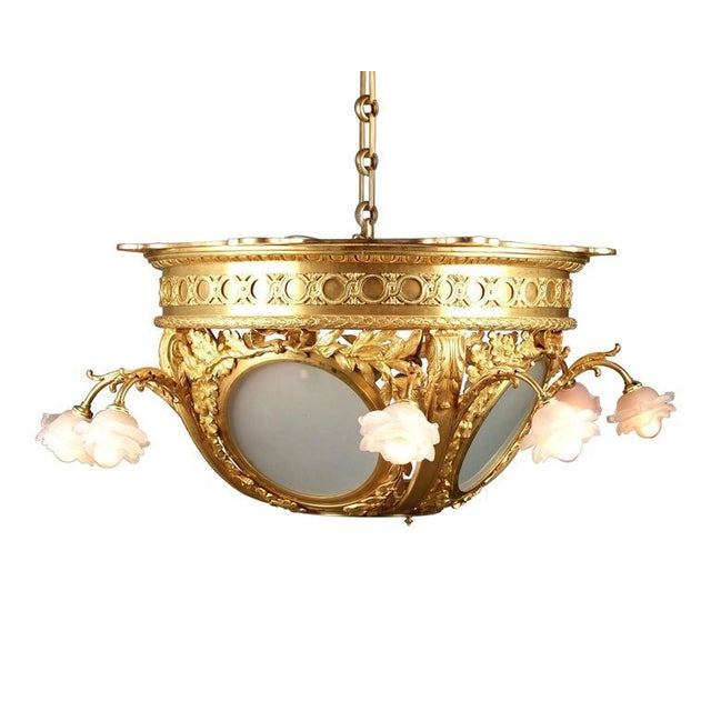 An absolutely stunning French doré bronze chandelier with four double-light frosted glass rosette shades and a central...
