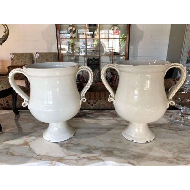 Lovely pair of white ceramic urns with lids by Fortunata Made in Italy. Terrific distressed, aged look. Shown here with...