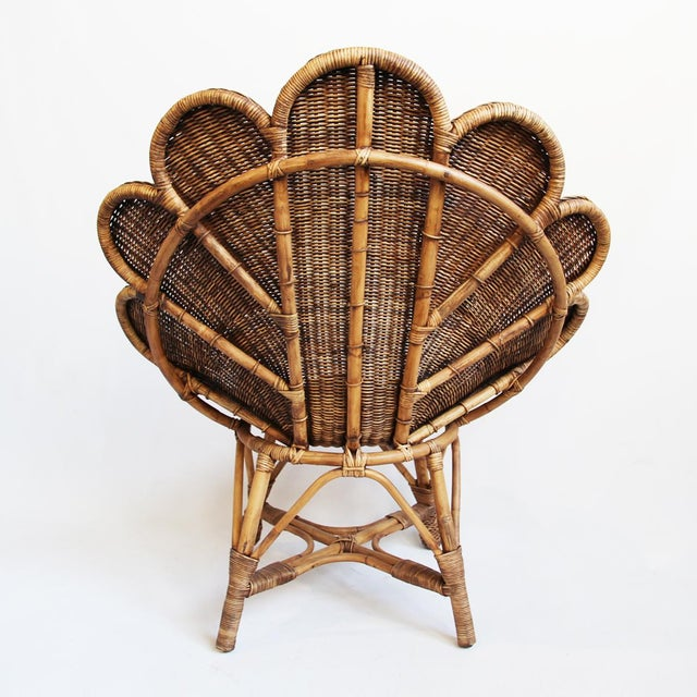 Hand woven rattan shell shaped occasional chair with antiqued stained finish. Beautiful and fun seating option for indoors...