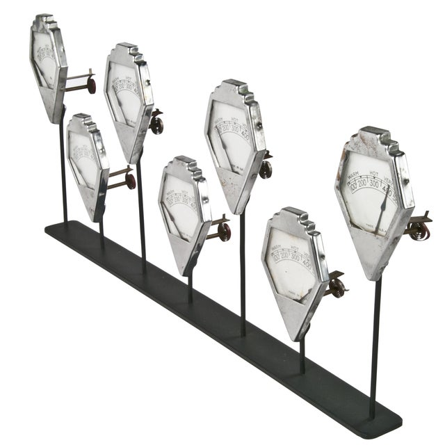 Group of seven vintage temperature gauges mounted on a reclaimed iron stand for display.