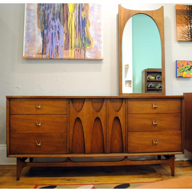This is an iconic Mid-Century Modern sculpted walnut nine-drawer dresser by Broyhill Furniture Co. This is from the very...