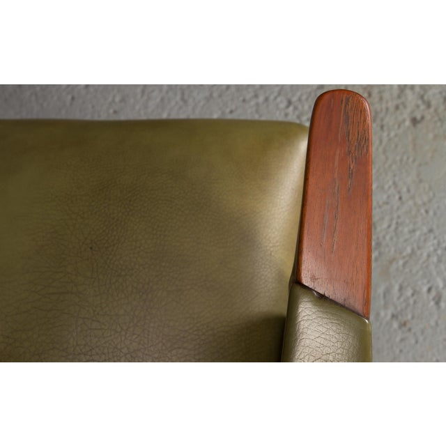 Danish modern lounge chair in green leatherette with nail heads and teak paws. Made in the 1950s.