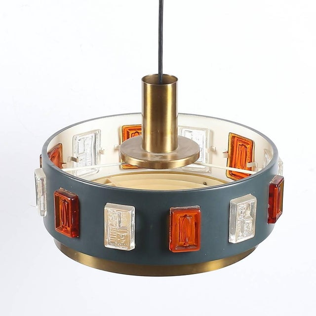 A pendant by Erik Hoglund, Sweden, circa 1970. Brass, paint metal and hand blown glass decoration. Existing wiring,...