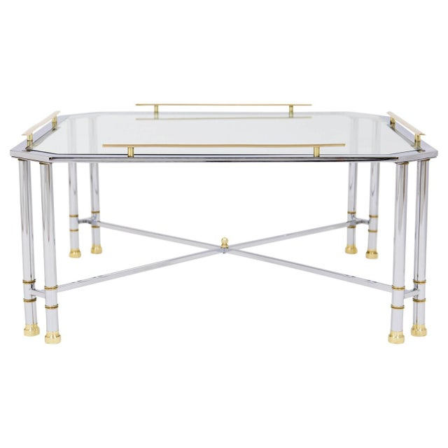Vintage chrome cocktail table with glass top and brass accents, attributed to Maison Jansen. It is square with clipped...