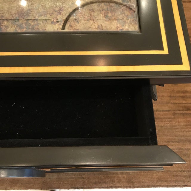 This side table is black with gold accents with an antique mirror top. The best is a surprise drawer in the front, open...