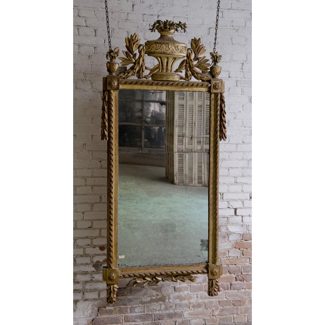18th Century Louis XVI Mirror, carved gilt wood, Provenance France. This mirror is adorned with floral and foliate...