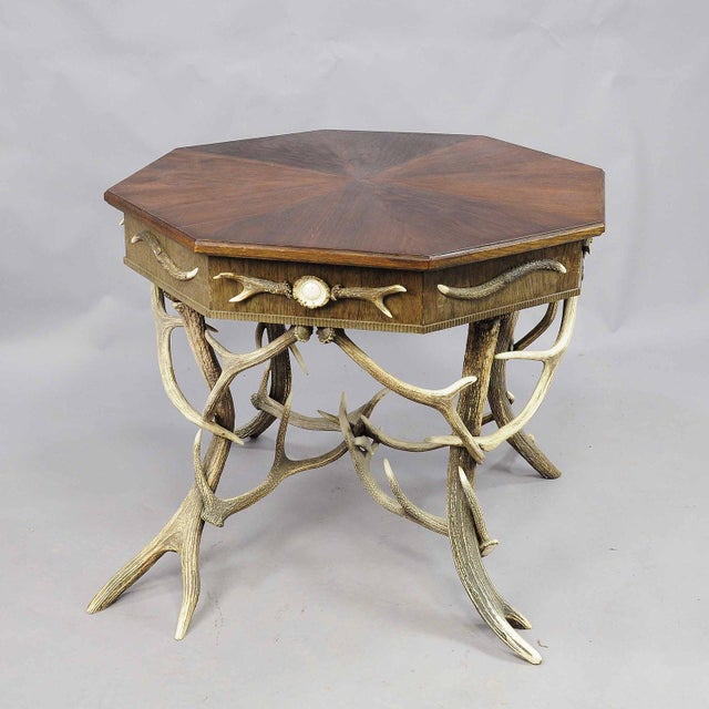 An antique octagonal antler table. decorated with several antlers from the deer and stag. Each corner with turned horn...