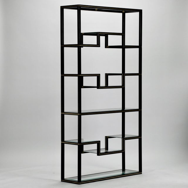 Mid Century black lacquered metal etagere by French designer Pierre Vandel featuring brass inset trim on the frame and...