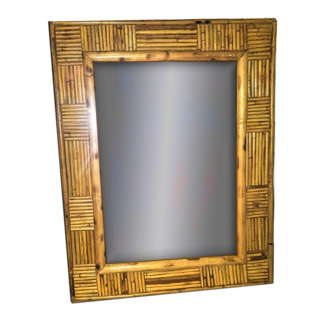 This 1950's bamboo pencil reed rattan patchwork designed frame surrounds a rectangular shaped accent wall mirror. The...
