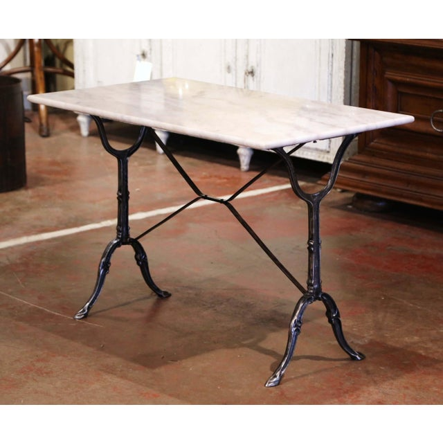Crafted in France circa 1920, the antique cast iron table sits on a trestle base with elegant scroll legs, joined with a...