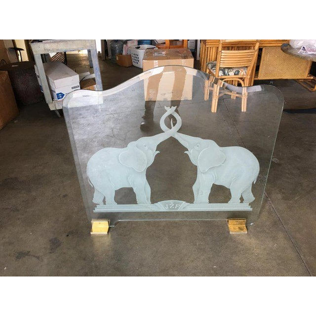 """""""Lovers"""" fireplace screen featuring an image of entangled elephant lovers etched into 1/2"""" thick green edge glass with..."""