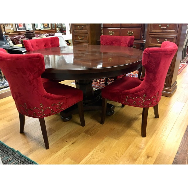 Stunning round Bernhardt mahogany dining room table with one leaf measuring 24 inches. Comes with upholstered red chairs...