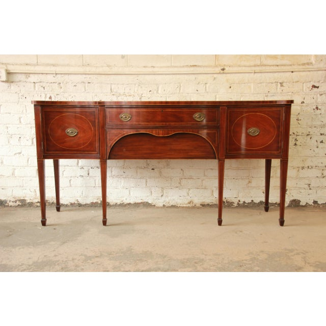 Offering a gorgeous vintage Hepplewhite inlaid mahogany sideboard by Kittinger. The sideboard features beautiful mahogany...