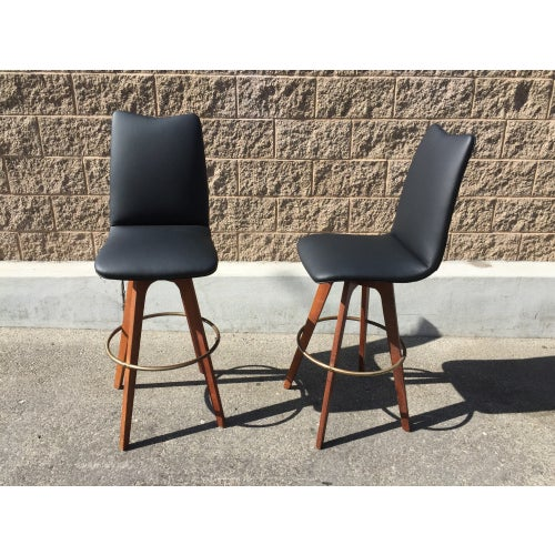 A nice pair of mid century walnut swivel barstools designed by Chet Beardsley. It has new black vinyl upholstery with...