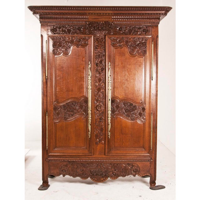 An early 19th century French marriage armoire with wide carved panels of flowers and grapes on the tops of the doors. The...