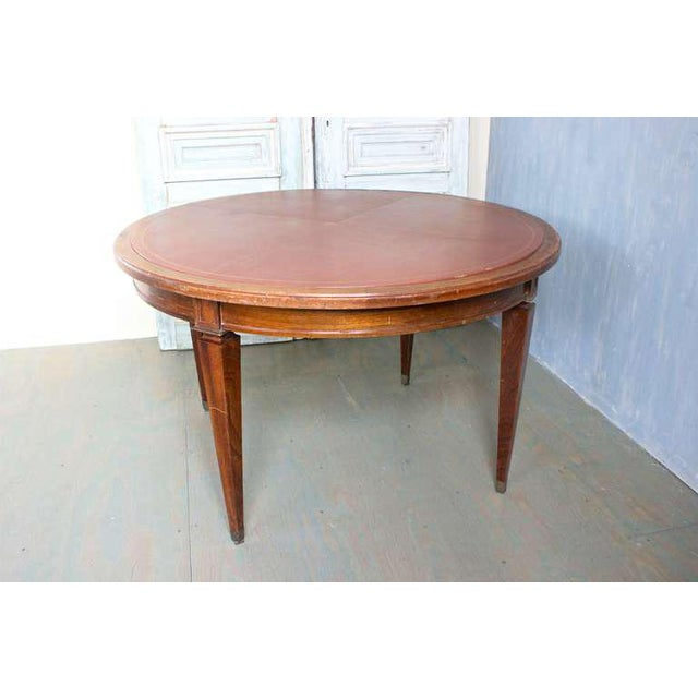 French 1940s mahogany card table with leather inset that had gold tooling border. The legs have brass sabot. This piece is...