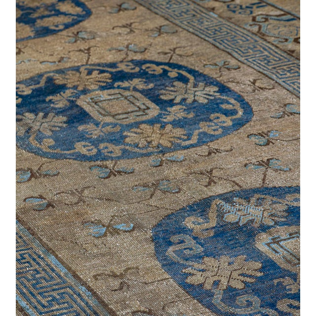 This antique Khotan rug has a dusty sandy-brown field scattered with delicate light blue and golden-yellow delicate...