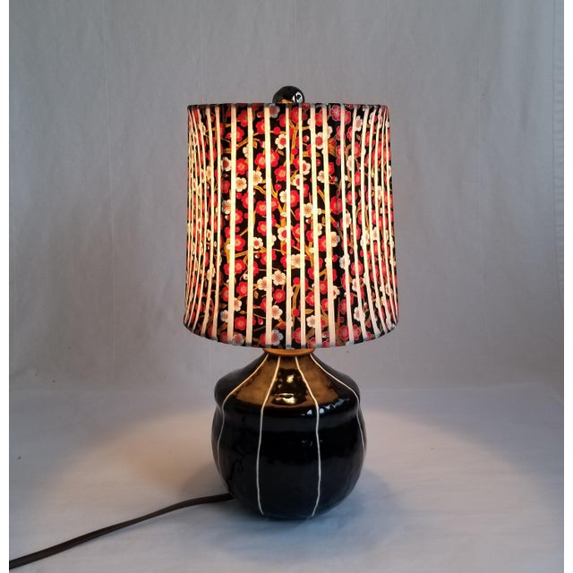 Handmade ceramic lamp glazed in glossy black with thin, raised white stripes. It's chubby, acorn shape is just the right...