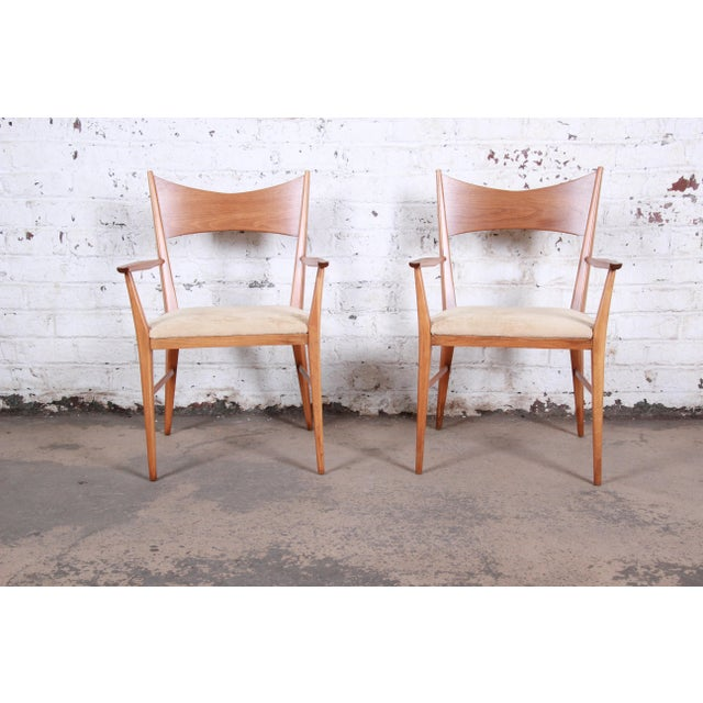 An exceptional pair of mid-century modern sculpted walnut bow tie armchairs designed by Paul McCobb for Calvin Furniture....