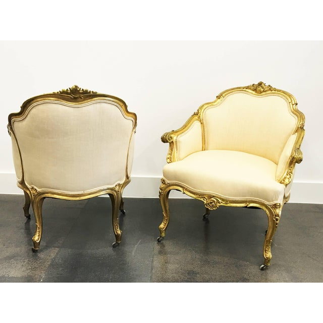 A wonderful pair of 19th century Louis XV giltwood bergeres. Features a carved giltwood frame. Raised by elegant cabriole...