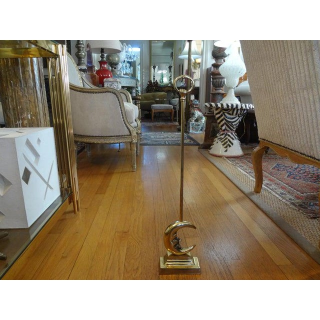 Charming Hollywood Regency brass doorstop terminating in a moon with a hand held handle. A great decorative accessory!