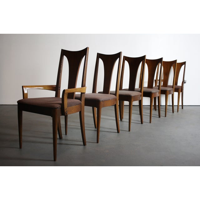 Set of six Broyhill Brasilia dining chairs in walnut. Includes two captain's chairs. The seller says: The Broyhill...